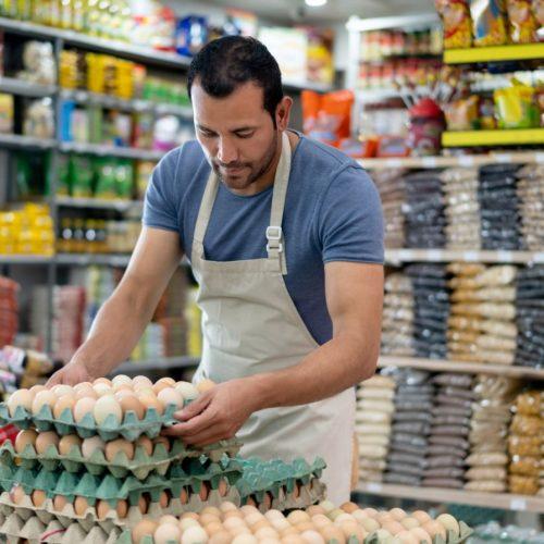 Ein Mann räumt Eier im Supermarkt ein.