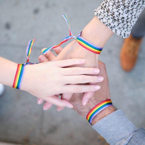 LGBTQ-Ally mit Regenbogen-Armbändern.