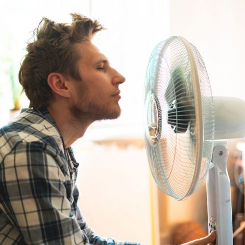 Ein Mann kühlt sich vorm Ventilator ab.