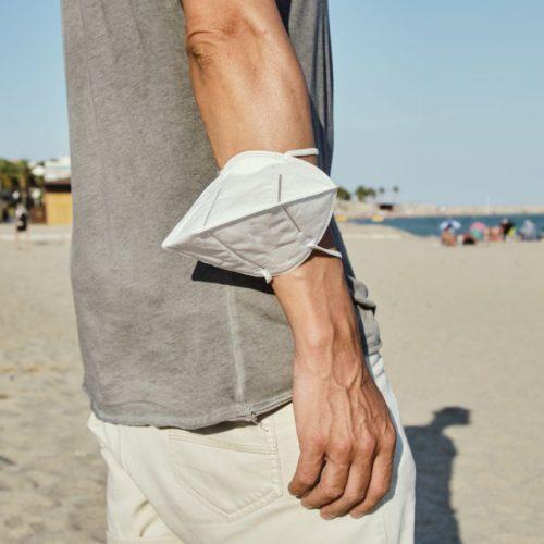 Mann mit Maske um den Arm am Strand