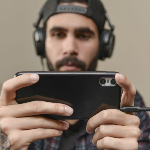 Mann spielt auf dem Smartphone