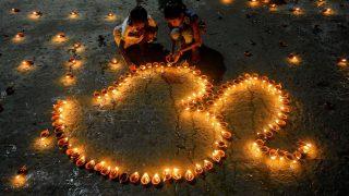 Kinder entzünden Lichter zu einem Om-Zeichen