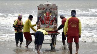 Hindus bringen eine Figur ihres Gottes Ganesha ins Wasser