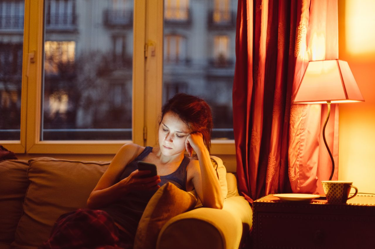 Frau sitzt einsam auf der Couch
