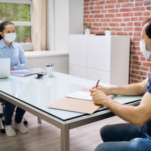 Ein Bewerbungsgespräch in Corona-Zeiten mit Abstand und Masken.